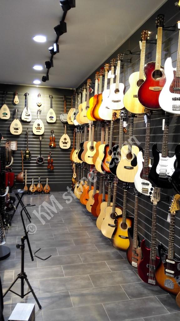 Επένδυση-τοίχου-με-σλατ-πάνελ-για-κρέμαση-προιόντων-κιθάρες-575x1024.jpg